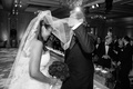 black and white photo of father of the bride lifting vera wang blusher veil of bride