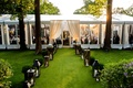 Backyard wedding lawn with wood lanterns leading to clear tent reception space