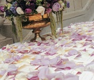 Escort cards on table sprinkled with flower petals and urn arrangement