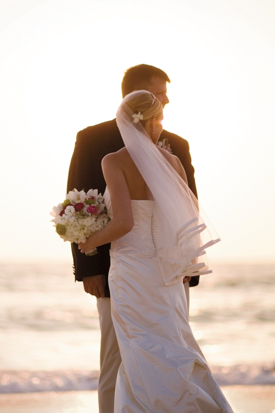bride and groom stand on sand at sunset