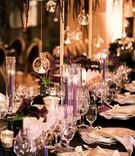 wedding reception with darker colors, purple tapered candles, black linens, glass globes