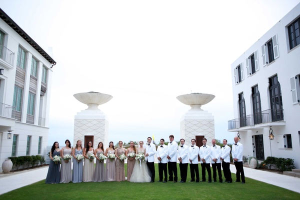 wedding party different bridesmaid dresses white suit jackets hotel courtyard ocean