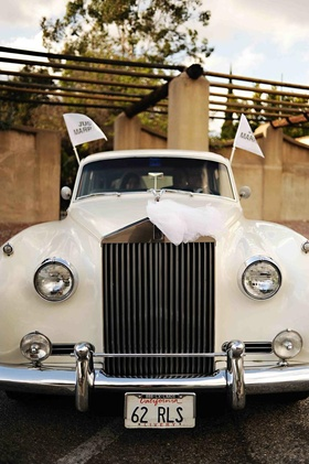 Ivory vintage car with Just Married flags
