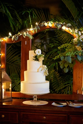 White wedding cake decorated with greenery and flowers
