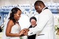Brooklyn African American couple at wedding ceremony woman officiant orchid flowers white strapless