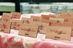 Wood place cards on a pink-and-white print tablecloth
