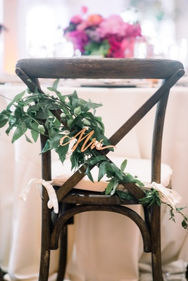 "rose gold laser-cut ""Mrs."" on greenery for bride chair decoration"