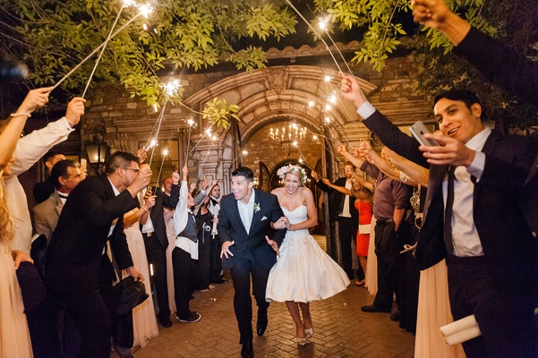 Bride in second wedding dress short with groom going through guest sparkler tunnel outdoors