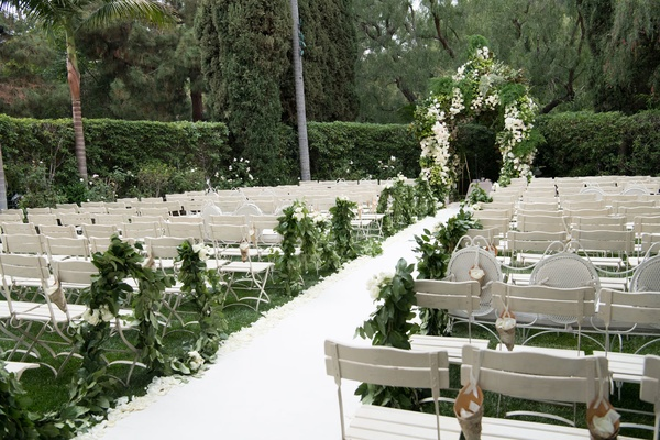 Green garlands weaving through ceremony chairs along aisle runner white flower petals outdoor