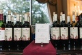Wine bottles at Oheka Castle wedding reception with card menu his and hers drinks