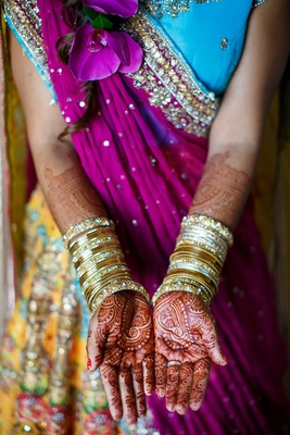 bride with henna on hands and gold bangles and colorful outfit blue purple yellow