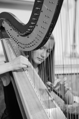 Black and white photo of woman playing harp
