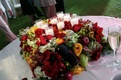 Candles on top of fruit and flower centerpiece