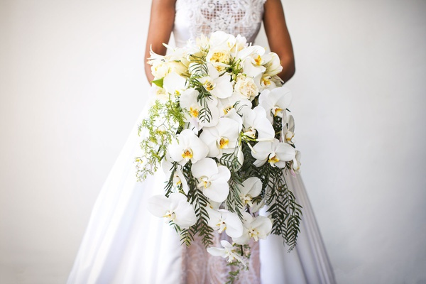 Bride in wedding dress a line holding large cascade bouquet with orchid flowers fresh greenery