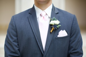 Groom's boutonniere with white flower and thistle plants grey suit light pink tie