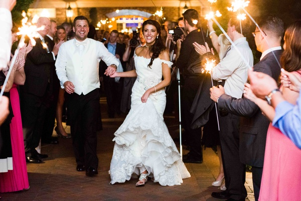 Bride and groom run through tunnel of guests with sparklers