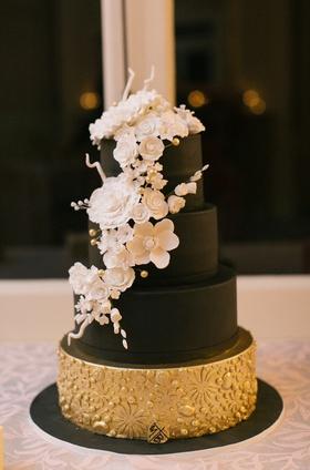 black wedding cake with fake layers, white sugar flowers