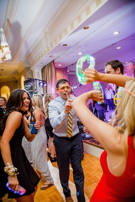wedding guests dancing and partying with glow sticks