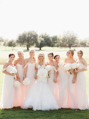 Bride in trumpet gown with large white bouquet and bridesmaids in light pink off shoulder long dress