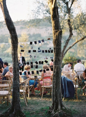 wedding reception family photos on string between trees guests at outdoor reception rattan chairs