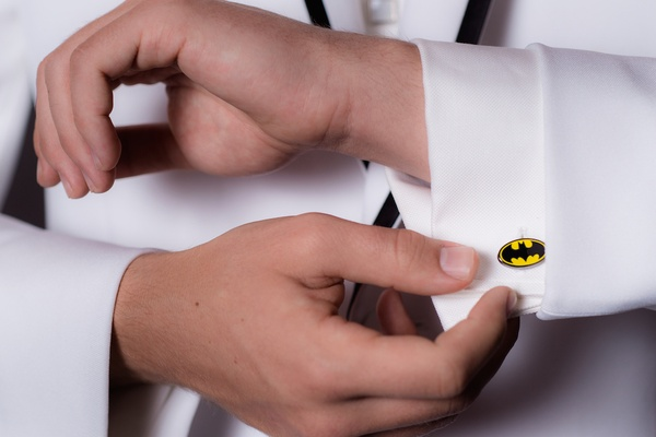 Wedding guest in white tuxedo jacket wears batman logo cuff link with white shirt