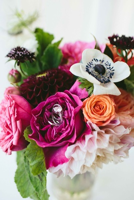 ranunculus blossoms, anemones, dahlias, and garden roses engagement ring in center