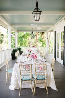 wedding reception wraparound porch southern destination wedding pastel color palette gold chairs