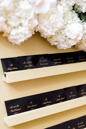 wedding reception escort card glossy black paper with gold calligraphy on floating shelf flowers