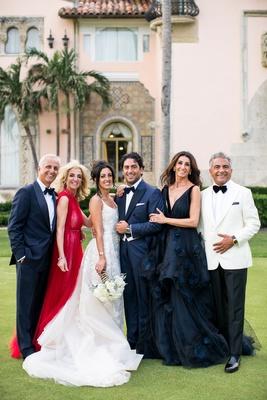 bride and groom with parents in formal wedding attire jewish wedding red dress dark midnight gown
