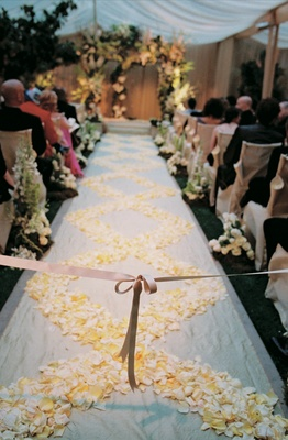 White aisle runner decorated with white and yellow rose petals