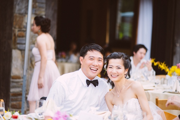 Chinese bride and groom sitting at outdoor table