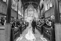 black and white photo of bride walking down aisle with father lace gown train church ceremony