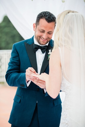 groom in navy brooks brothers tuxedo putting ring on bride's finger during the ceremony