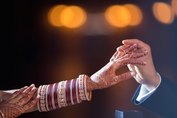 Groom puts diamond wedding ring on Indian bride's hand with henna and bracelets