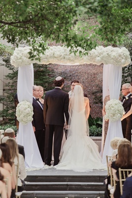 Bride in  low back mermaid wedding dress and groom in suit and yarmulke under chuppah white drapery