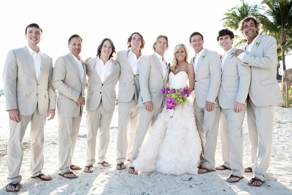 Beach wedding bride with groom and casual groomsmen