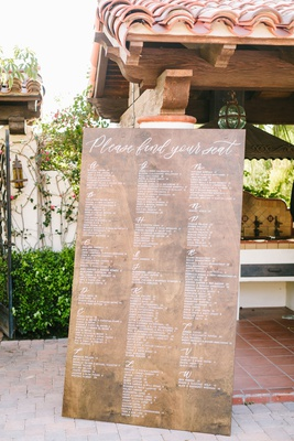 wedding reception spanish style venue large wood sign with white lettering alphabetic seating chart