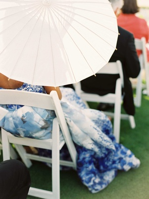 White sun umbrella parasol being held by ceremony guest in white chair on grass lawn