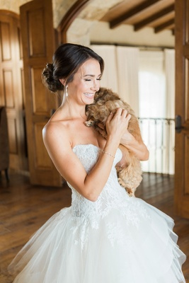 Bride in strapless monique lhuillier lace wedding dress ball gown holding small tan brown dog