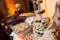Wedding dessert table with cupcakes on tiered stand, flan, swan desserts, cannoli treats