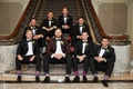 Groom in burgundy tuxedo jacket with groomsmen in tuxedos with funny fashionable socks