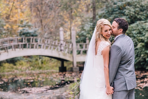 grooms kisses his bride on the cheek as they stand outside near a lake with a bridge