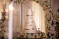 Wedding cake on round table with gold ribbon details under flower arch ivory sugar flowers