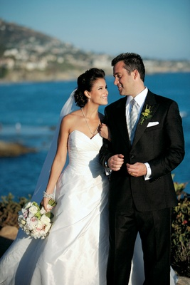 bride and groom gaze at each other with ocean background