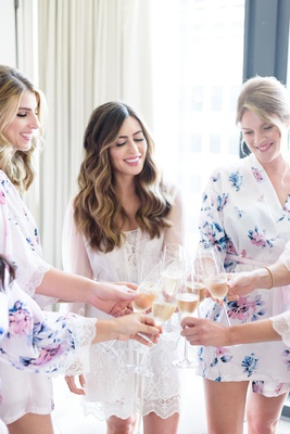 getting ready photo of bride and bridesmaids in robes toasting cheers champagne bridal suite