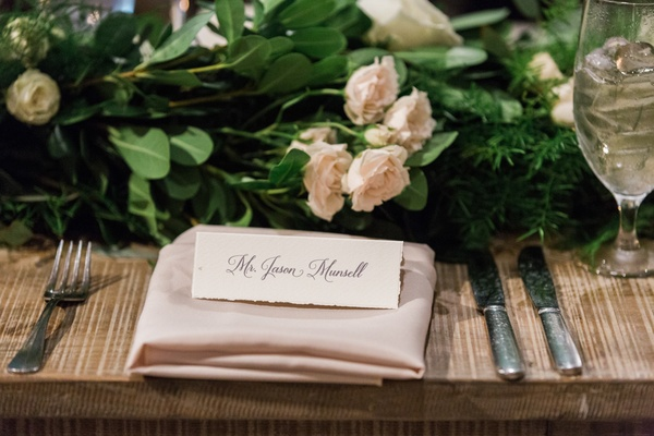 name cards on blush napkin with blush flowers and green leaves and silverwear