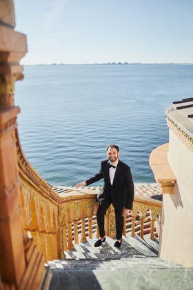 groom in tuxedo and slippers walking up steps of ca' d'van mansion