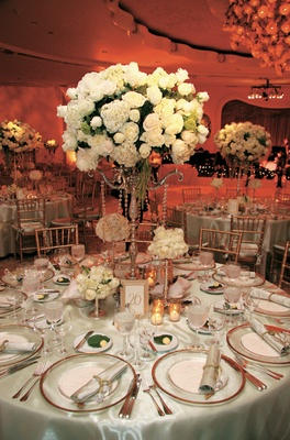 Wedding reception centerpiece of white roses and hydrangeas in a silver candelabra