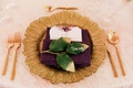 wedding reception place setting gold charger plate purple napkin green leaves place card flatware