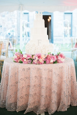 white wedding cake inspired by cinderella's caste, flowers on base, sparkling linen